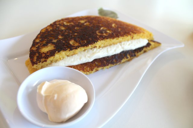 Las cachapas se prepara con maíz tierno amarillo molido al que se le añade leche o agua, azúcar, sal y aceite, hasta formar una mezcla semilíquida como si fuera un panqueque. La que aparece en esta foto es la cachapa de queso de mano. Otras opciones son las cachapas de queso y jamón; queso y frijoles negros; queso, nutella y plátanos maduros y la de queso y pollo rallado. Foto: Sylvia Obén