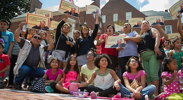 More than 50 people circled the governor's mansion in Annapolis on Thursday to protest Maryland Gov. Larry Hogan's decision to cooperate with federal officials in immigration enforcement efforts.