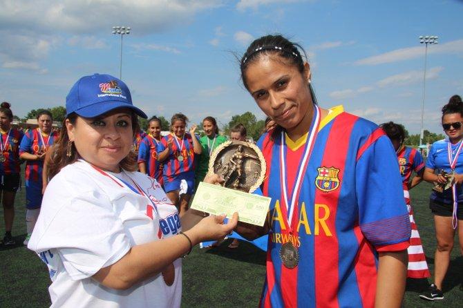 Una representante de la empresa patrocinante entrega a la capitana de Las Coronitas, Erika Guerra, el trofeo y premio por su campeonato en la American Soccer League de Herndon.