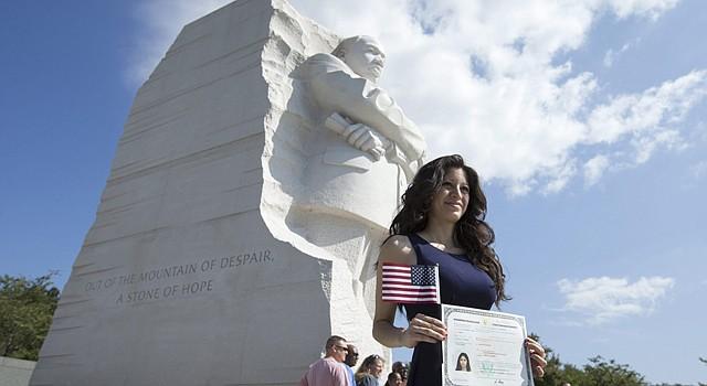 """La ciudadana estadounidense originaria de El Salvador, Judith Escobar, sujeta su certificado de Naturalización frente al monumento a Martin Luther King Jr., la """"piedra la esperanza"""" tras la ceremonia del servicio de ciudadanía estadounidense e inmigración en Washington DC, EEUU, hoy, 28 de agosto de 2015."""