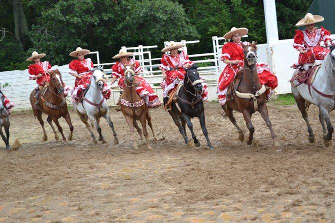 Las Amazonas del Dorado, realizando una de sus acrobacias sobre sus caballos.