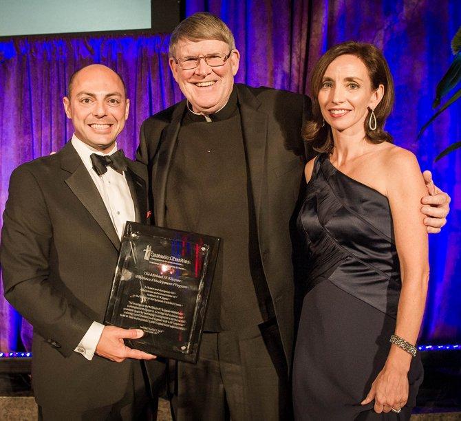 El CEO de Caridades Católicas, monseñor Enzler (centro) entrega un reconocimiento a William y Laura Kappaz quienes presidieron la gala del Centro Católico Hispano en el edificio Ronald Reagan de Washington.
