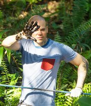 """René Pérez Joglar, conocido como Residente, y vocalista de la banda puertorriqueña Calle 13, muestra su mano con petróleo, el 2 de mayo de 2014, durante su visita al pozo """"Aguarico 4"""", en la provincia de Sucumbíos, una piscina con desechos tóxicos que dejó hace 26 años en la selva la petrolera Texaco, posteriormente adquirida por Chevron."""