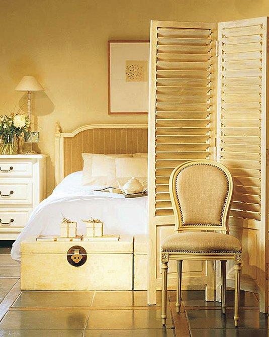 Coloque un biombo si necesita más privacidad. También es una solución muy práctica para separar la cama del vestidor o del rincón de lectura. El biombo y el resto de los muebles pueden ser de madera decapada.