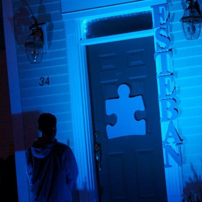 Esteban, hijo de Maribel Rueda celebrando el Mes del Autismo. El joven está afuera de su casa que está alumbrada de azul, color utilizado para solidarizarse con el Mes del Autismo.