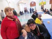 ABRAZO. La directora de OLA, abraza a una de las personas que llega habitualmente a cenar a la iglesia Sagrado Corazón. Al lado, Silvia Rodwan, de la Alianza Latina USA.