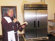 El padre Moisés Villalta bendice el refrigerador donado por Alianza Latina USA a la iglesia Sagrado Corazon, el 7 de abril de 2016. (Milagros Meléndez-Vela/ETL)