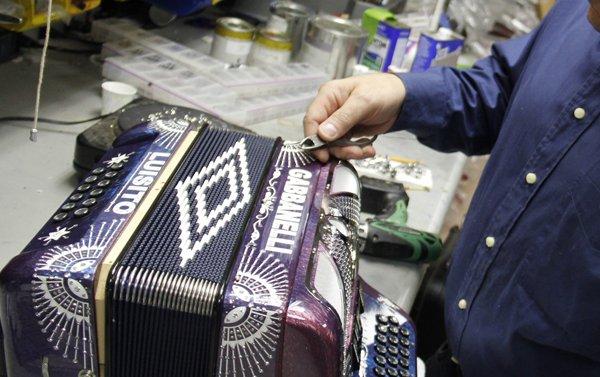 Los clientes pueden personalizar sus acordeones con diferentes colores, grabados e imágenes. Todo el trabajo se hace a mano. Aquí Mike Gabbanelli entalla los cristales Swarovski en uno de sus instrumentos.