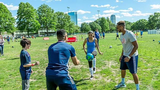 Estudiantes de The Hurley School, Yanifred Galarza  (13 años) y David Wetzel (13 años) practican fútbol con Charlie Davies y Darrius Barnes en la celebración del lanzamiento del programa Santander Soccer Scholars.