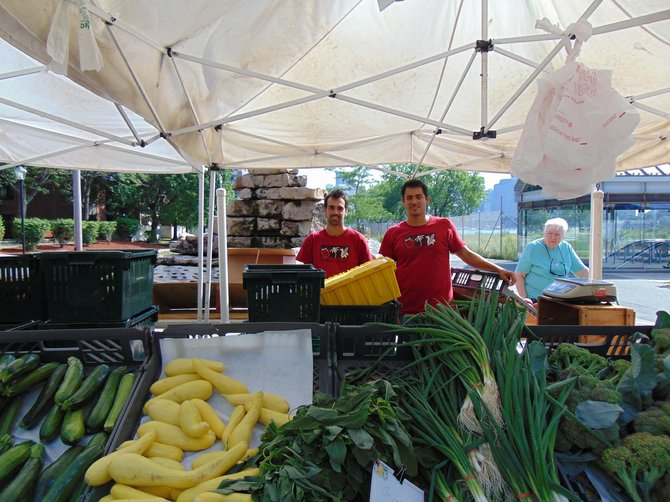 Joao Silva y Juan Pinto tienen un puesto de vegetales y frutas en el mercado de agricultores.