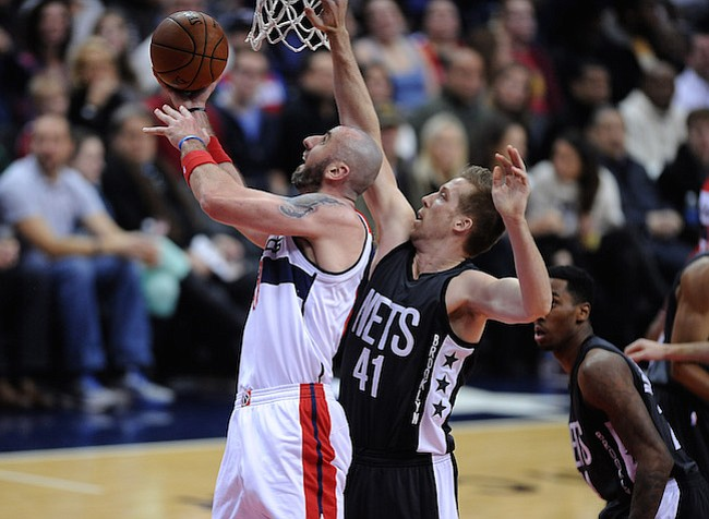 Washington D.C. -December 30, 2016: Marcin Gortat de los Washington Wizards se eleva con el balon para anotar en la canasta contra Justin Hamilton de los Brooklyn Nets. Los Washington Wizards derrotaron a los Brooklyn Nets 118-95 en un partido de la temporada regular en la arena de el Verizon Center.