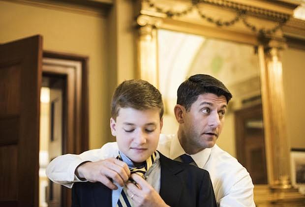 Mientras se reúne con su personal, el presidente de la Cámara de Representantes Paul Ryan, R-Wis., hace la corbata para su hijo de 13 años, Charlie, antes de las ceremonias de juramento en la Cámara en el primer día del 115 Congreso.