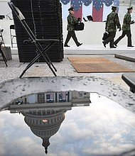 El capitolio de los Estados Unidos se refleja en un charco del agua en una silla mientras que la gente ensaya el domingo para la inauguración de Donald Trump.
