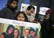 Giovani Jiménez, en el centro arriba, se limpia una lágrima mientras está rodeado por su hijo, Alex, de 13 años, y su hija Lucía, de 7 años, en una manifestación de CASA fuera de la oficina de Inmigración y Aduanas de Estados Unidos.