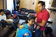Giovani Jiménez, a la derecha, cepilla el cabello de su hija Lucía, en el centro, mientras Alex espera a que se vayan a visitar a Uruchi en la cárcel regional de Virginia Peninsula en septiembre.