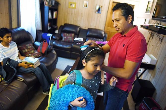 Giovani Jiménez, a la derecha, cepilla el cabello de su hija Lucía mientras Alex espera para ir a visitar a Uruchi en la cárcel regional Virginia Peninsula en septiembre. Ella será deportada esta semana.