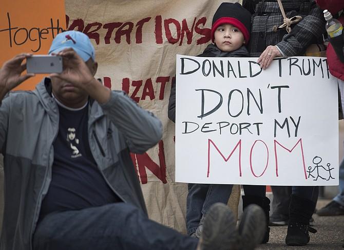 Un muchacho joven y su madre asisten a un rally en la plaza de Lafayette en el Districto de Columbia para protestar las recientes redadas a nivel nacional ICE.