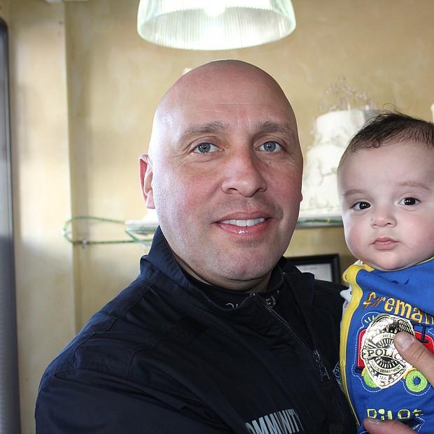 Sammy Mujica, oficial encargado de Servicios Comunitarios en la Policía de Chelsea, cargando un bebé de una vecina de Chelsea.