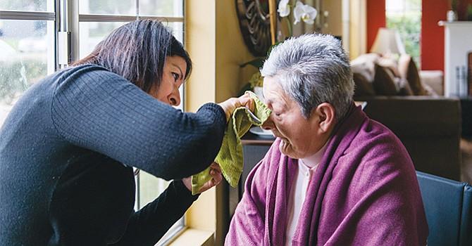 Tania Yanes hija le limpia la cara a su madre Blanca Rosa Rivera. (Heidi de Marco/KHN)