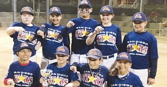 Los jugadores del equipo de béisbol San Diego Stars RED-11U, muestran el trofeo de campeones y los anillos obtenidos en el torneo realizado en Peoria, Arizona.Foto-Cortesía.