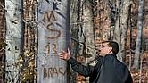El teniente Dave McClintock de la Policía de Parque del condado de Montgomery mira un signo la MS-13 tallado en un árbol en un bosque de Silver Spring, Maryland, en 2007.