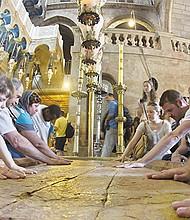 Varios peregrinos cristianos tocan la Piedra de la Unción a la entrada de la Iglesia del Santo Sepulcro, el lugar de la crucifixión, entierro y resurrección de Cristo, durante la Semana Santa en JerusalÈn. EFE/Jim Hollander