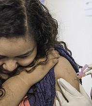 Ruth Marroquin, de 13 años, mira hacia otro lado mientras está vacunada contra el VPH.