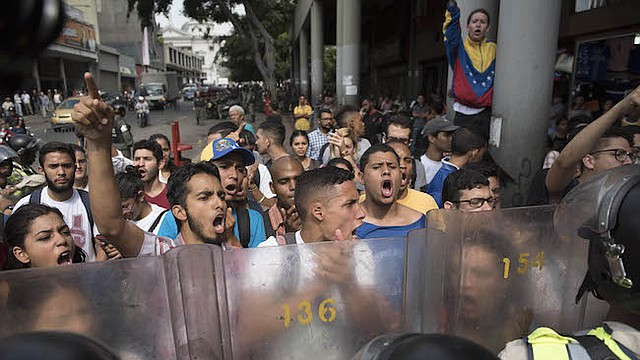Los manifestantes anti-gubernamentales enfrentan a los oficiales de la guardia nacional durante una protesta contra la decisión de la Corte Suprema de tomar los poderes del Congreso liderado por la oposición en Caracas, Venezuela, el 31 de marzo de 2017.