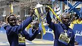 El kenianos Geoffrey Kirui (d) y Edna Kiplagat (i) celebran con el trofeo su victoria en la categoría masculina de la maratón de Boston, Massachusetts, Estados Unidos hoy 17 de abril de 2017.
