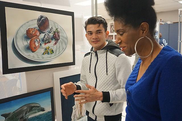 Rafael Rodriguez, 21, habla acerca de su trabajo con la profesora de arte Harolyn Andrews de la Escuela Secundaria Noroeste durante la exhibición.