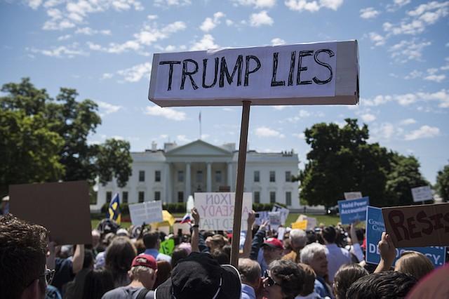 La gente lleva carteles durante una protesta frente a la Casa Blanca el 10 de mayo.