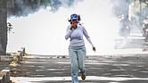 Una mujer huye de los gases lacrimógenos lanzados por las fuerzas de seguridad durante una protesta opositora el sábado 3 de junio, en Caracas, Venezuela.