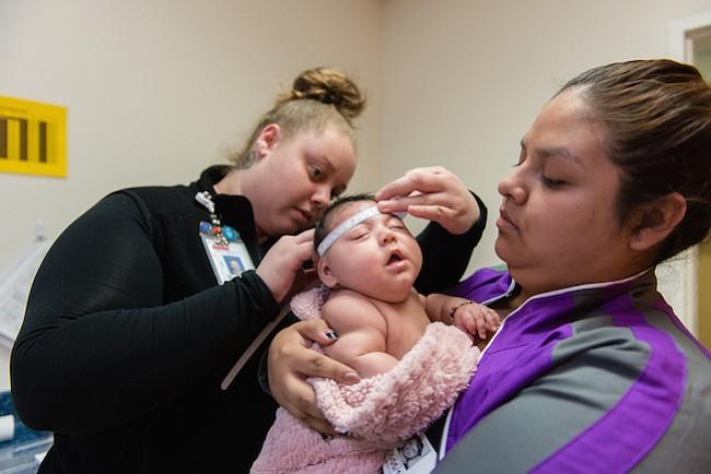 Jessica Rios sostiene a su sobrina Aryanna Guadalupe Sánchez-Ríos mientras un técnico que mide el cráneo del bebé en el Hospital de Niños de Seattle el 5 de mayo de 2017. A los 3 meses de edad, su cabeza era todavía más pequeña que la media.