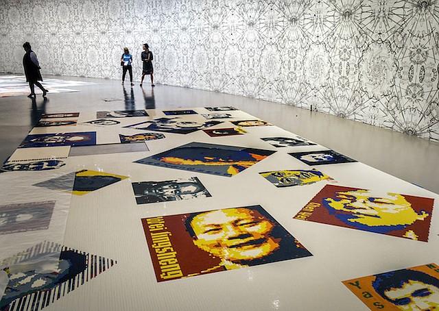 """En """"Trace"""", los ladrillos de Lego crean imágenes pixeladas de 157 hombres y 19 mujeres de 30 países, entre ellos Nelson Mandela, Martin Luther King Jr., la periodista rwanesa Agnes Uwimana Nkusi y disidente chino y ganador del Premio Nobel de la Paz Liu Xiaobo."""