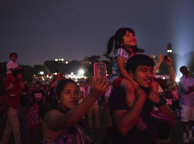 Izabel Yac disfruta los fuegos artificiales en los hombros de su padre en el Monumento de Washington en Washington, D.C.