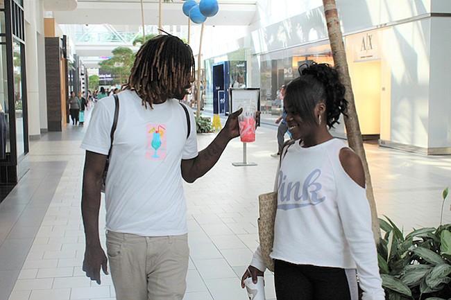 Maya Terrell, a la derecha, camina con Lamarr Morris en el centro comercial Arden Fair de Sacramento el 19 de junio.