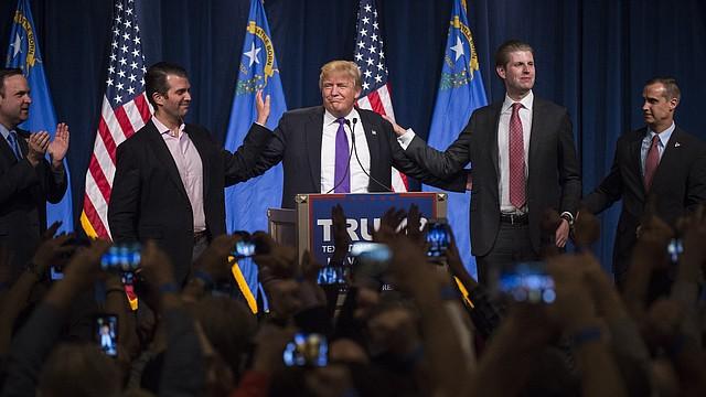 Donald Trump, en el centro, habla durante un acto de la campaña electoral en Las Vegas el 23 de febrero de 2016. Sus hijos Donald Trump Jr., a la izquierda, y Eric, a la derecha, abrazan a su padre en el escenario.