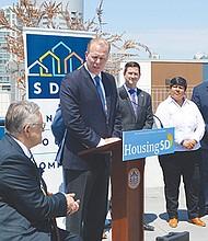 El alcalde Kevin Faulconer, durante la conferencia de prensa, confirma un dato con Richard C. Gentry, presidente de SDHC (sentado). Horacio Rentería/El Latino San Diego.