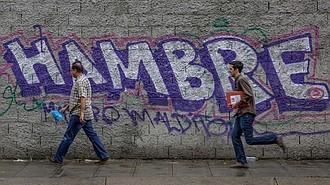 Transeúntes caminan por una calle bloqueada por manifestantes opositores. Analistas consideran que sanciones contra la industria petrolera de Venezuela podrían empeorar la crisis humanitaria.