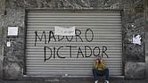 """Un hombre se sienta frente a un graffiti que lee """"Dictador Maduro"""" durante una huelga nacional en el distrito de Chacao de Caracas, Venezuela, el 20 de julio de 2107."""