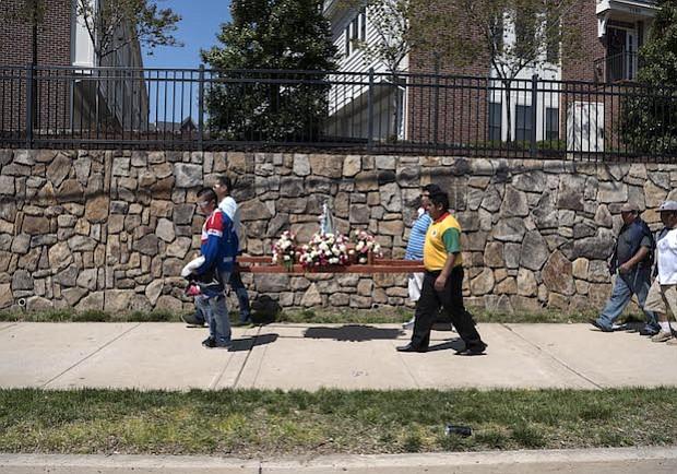 """VIRGEN. Miembros del Comité Pro Bolivia cargan la Virgen de Socavón durante el carnaval de febrero 2016 caminando a lo largo del """"Four Mile Run"""" en Arlington, Virginia."""
