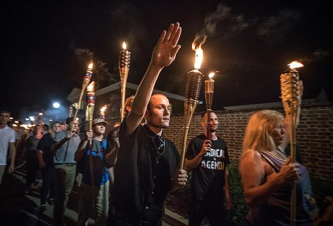 """Con cánticos como """"¡Las vidas de los blancos son importantes!"""", """"¡No nos reemplazarán!"""" y """"¡Los judíos no nos reemplazarán!"""", varios cientos de nacionalistas y supremacistas blancos llevando antorchas marcharon en un desfile por el campus de la Universidad de Virginia el 11 de agosto."""