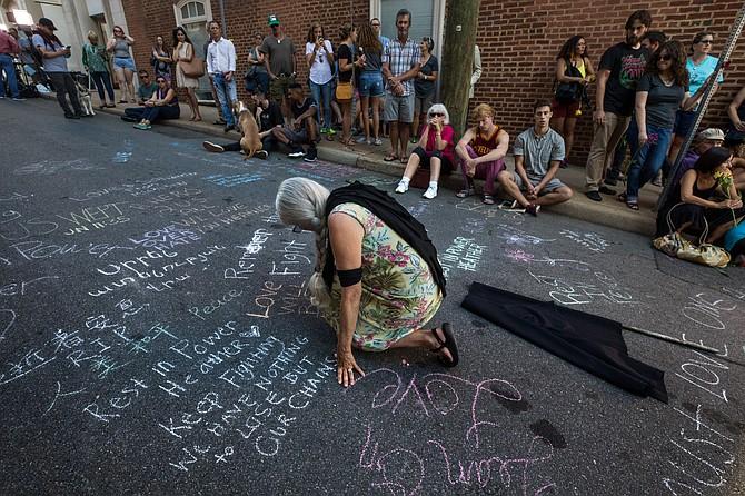 Lise Stoessel, de Charlottesville, Virginia, escribe un mensaje el domingo en el monumento en el sitio del ataque mortal del coche allí un día antes.