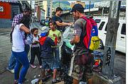 MISERIA. Hombres, mujeres y niños registran la basura en las calles de Venezuela para tratar de encontrar algo de comer.