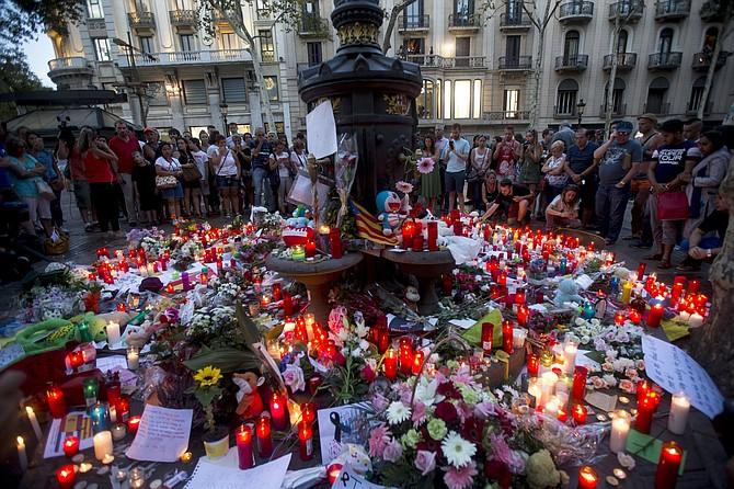 Decenas de personas han acudido esta noche a la fuente de Canaletas, en las Ramblas, donde a lo largo del día se han ido depositando flores y velas en memoria de las víctimas del atentado de ayer en este enclave de la ciudad.