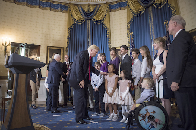 """El presidente Donald Trump saluda a """"las víctimas de Obamacare"""" después de hablar en un evento de la Casa Blanca sobre la atención de la salud a finales de julio. La retórica y los esfuerzos de la administración reflejan su enfoque contradictorio de la próxima temporada de inscripción de la ley, que comienza el 1 de noviembre."""