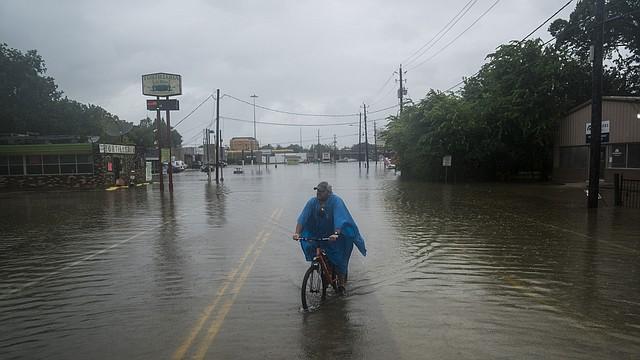 Un hombre monta su bicicleta a lo largo de Mercury Drive en Houston durante la tormenta tropical Harvey.