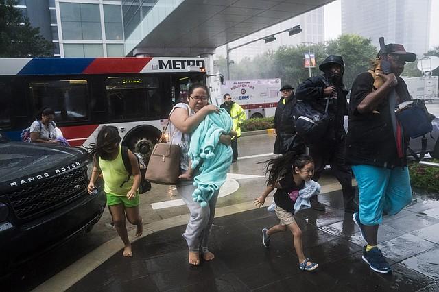 Las personas rescatadas salen de los autobuses hacia el Centro de Convenciones George R. Brown de Houston.