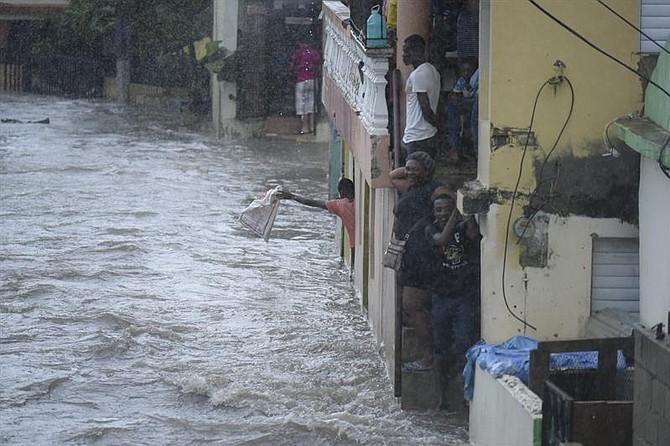 Personas observan una calle inundada el 7 de septiembre, en Santiago de los Caballeros, República Dominicana. Lluvias y vientos desde las 3:00 a.m. de este día inundaron la calle 4B y 11 del sector Hoya del Caimito, donde al menos 150 casas quedaron inundadas por la crecida del arroyo que cruza por esta barriada. Más de 5.500 personas han sido evacuadas en República Dominicana a causa del poderoso huracán Irma.