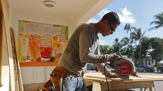 Hector Díaz corta madera que se utilizará para cubrir ventanas en este restaurante Ocean Drive en el extremo sur de Miami Beach antes de la llegada prevista del huracán Irma en Florida.